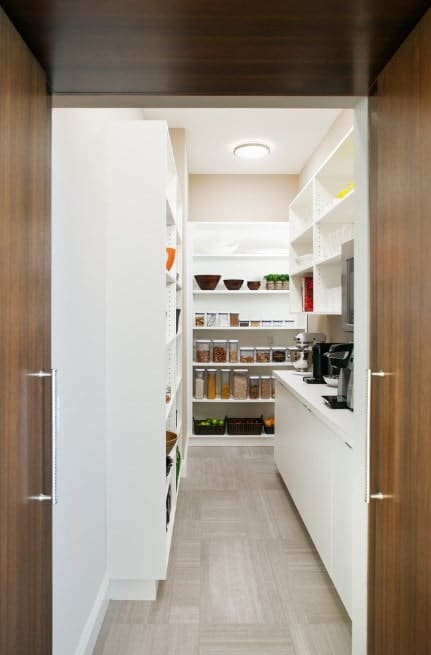 A narrow walk-in pantry featuring white shelving, white counter and a white countertop.