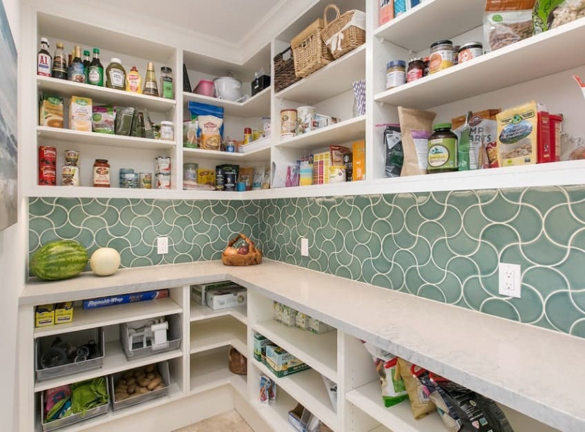 This pantry features very beautiful backsplash. This add style to this pantry with white shelving and counters with marble countertops.