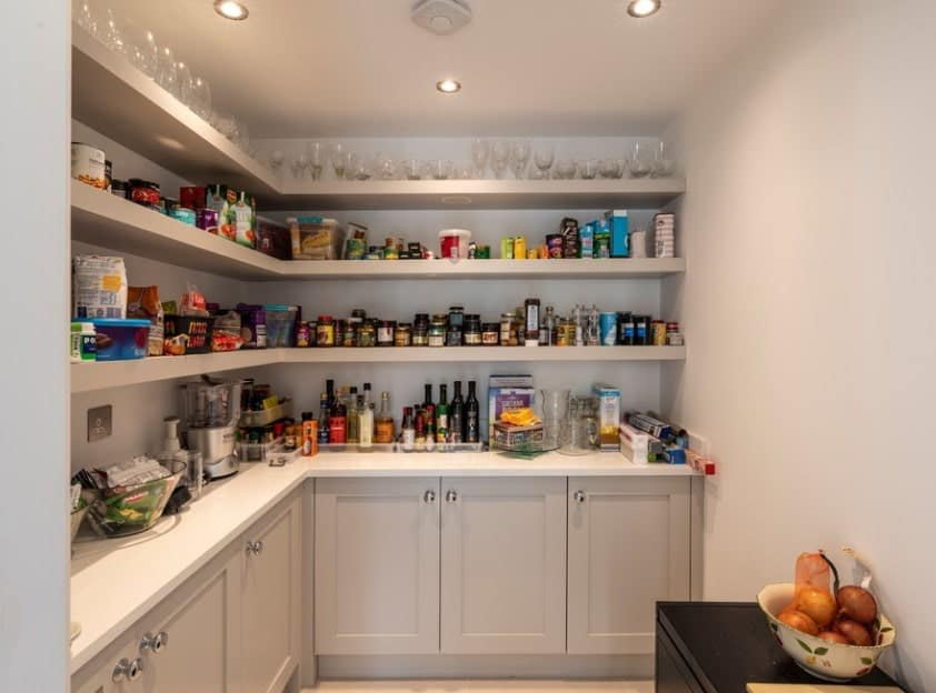 Large walk-in pantry with white walls, white shelves and white counters along with its white countertops.
