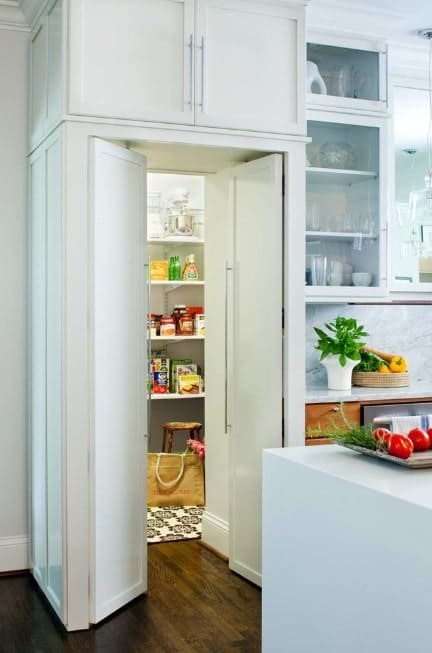 This kitchen features a small pantry with white doors and shelves.