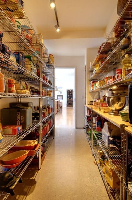 A narrow walk-in pantry lighted by track lights.
