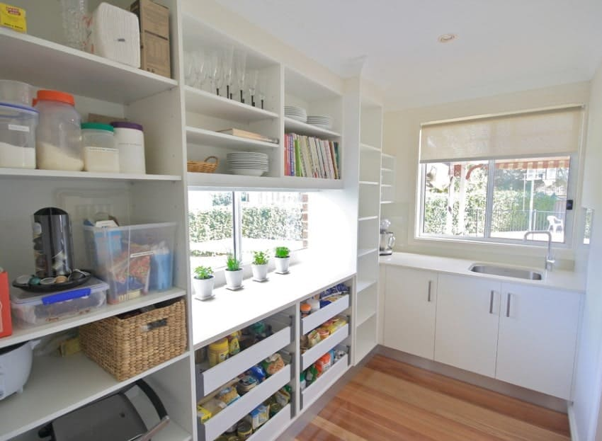 This walk-in pantry features a counter with white countertop and a sink. The flooring looks like a perfect fit with this pantry.