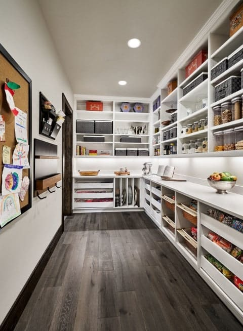 This modish pantry features white shelving, walls and counters along with a rustic shade from the hardwood flooring and the door.