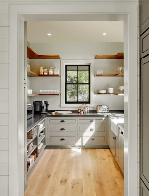 Large walk-in cabinetry featuring white counters with black countertops. The walnut finished shelves match with the hardwood flooring.