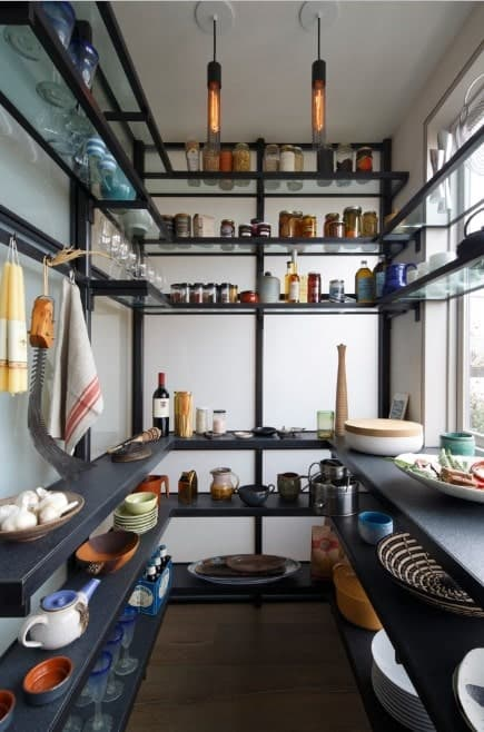 This pantry offers stylish counters and shelves along with an elegant pair of ceiling lights.