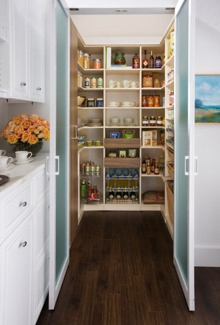 A small walk-in pantry featuring white shelves and a hardwood flooring.