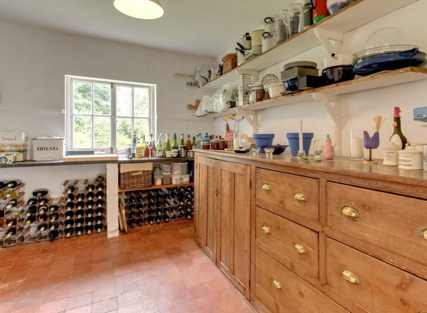 A large walk-in pantry with reddish tiles flooring along with walnut finished cabinetry and shelving. There's also a wine cellar on the side of the room.