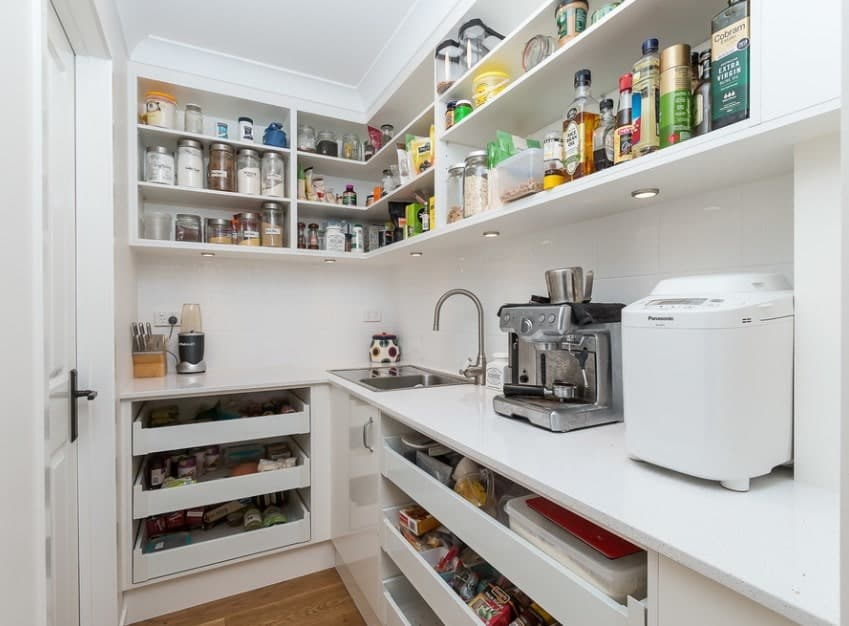 This walk-in pantry features white cabinetry, white shelving and smooth white countertops. It also features recessed lights installed on the shelving.