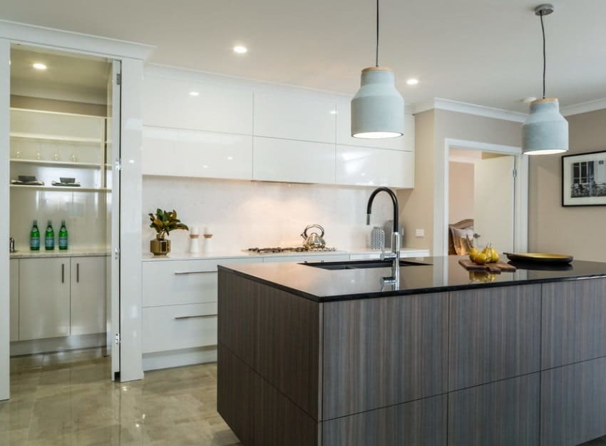 A modish kitchen featuring beautiful tiles flooring and a stylish center island with a pair of pendant lights. There's a pantry on the corner as well, featuring white counters and marble countertops.