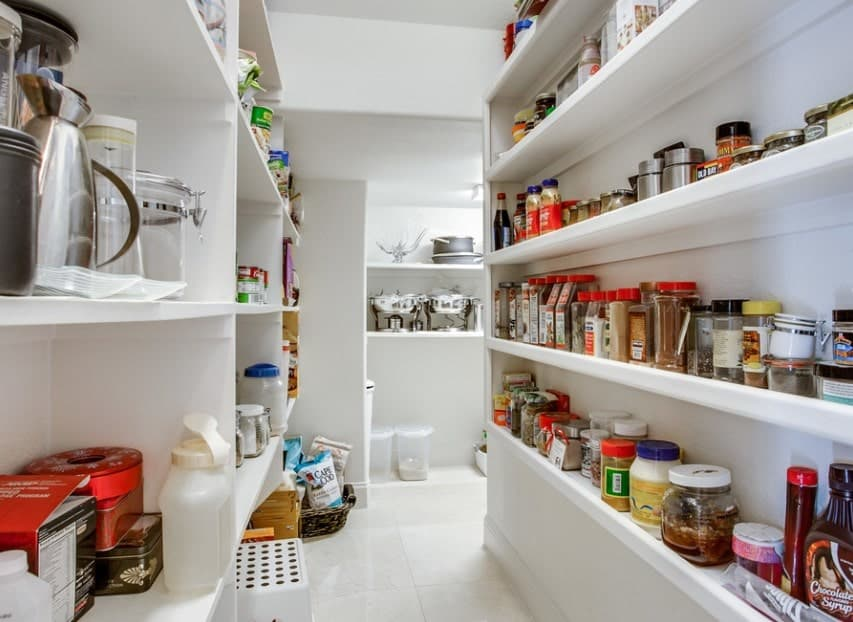 Large walk-in pantry with white walls, white cabinetry and white tiles flooring.