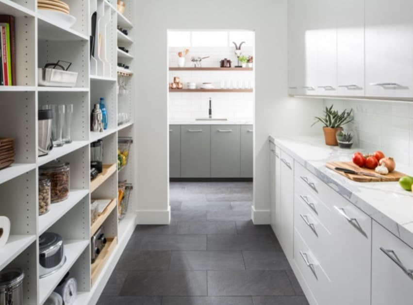 Large walk-in pantry with white walls and cabinetry. The white counters are equipped with a smooth white marble countertop.