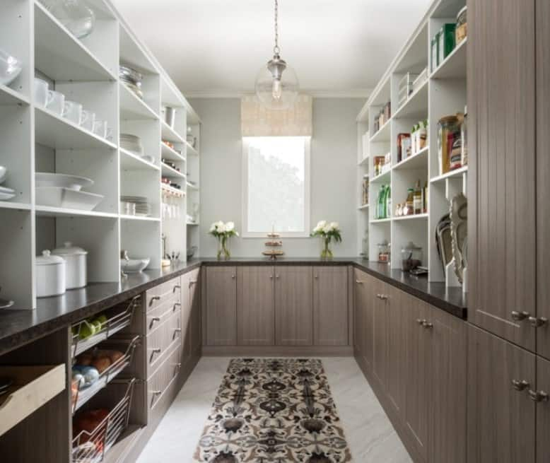 This large walk-in pantry features rustic finish counters with granite countertops. This pantry is lighted by a glamorous pendant lighting.