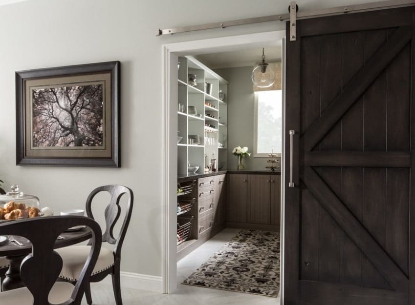 This walk-in pantry features a wooden sliding door along with rustic finished counters with granite countertops.