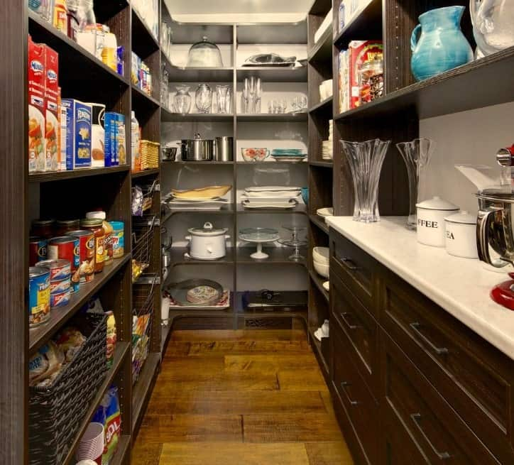 This narrow walk-in pantry features hardwood flooring that matches the wooden counters and shelving.