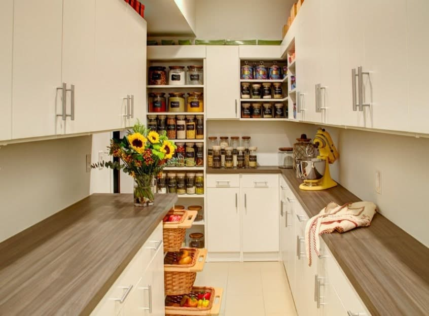 This pantry boasts pretty countertops with a lovely indoor plant. The white cabinetry looks just perfect for this room.