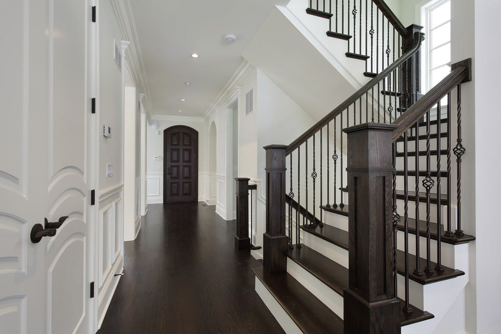 This elegant foyer is dominated by the white wooden walls, wainscoting, white wooden doors and the white ceiling with recessed lights. These are further brightened with its contrast to the dark hardwood flooring, wrought iron railings and the wooden banisters of the stairs.