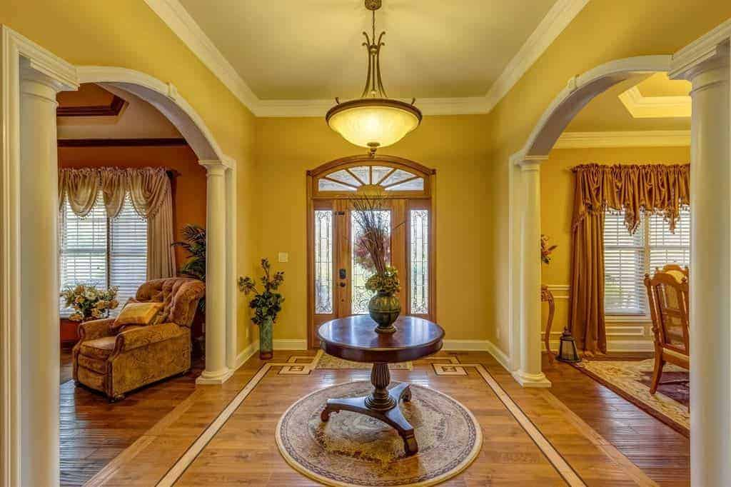 The sunny yellow walls of this charming foyer is complemented by the bright yellow glow of the dome pendant light hanging over the round wooden table. This is standing on a round area rug that accents the hardwood flooring along with the border lining from the doorway.