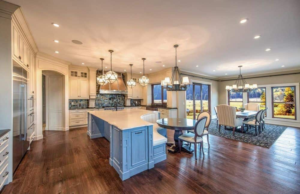 The kitchen has a beautiful hardwood flooring contrasted by the light gray wooden kitchen island that has a built in booth-style bench for the informal dining beside it. These are all topped with gorgeous pendant lights that throw a warm glow.