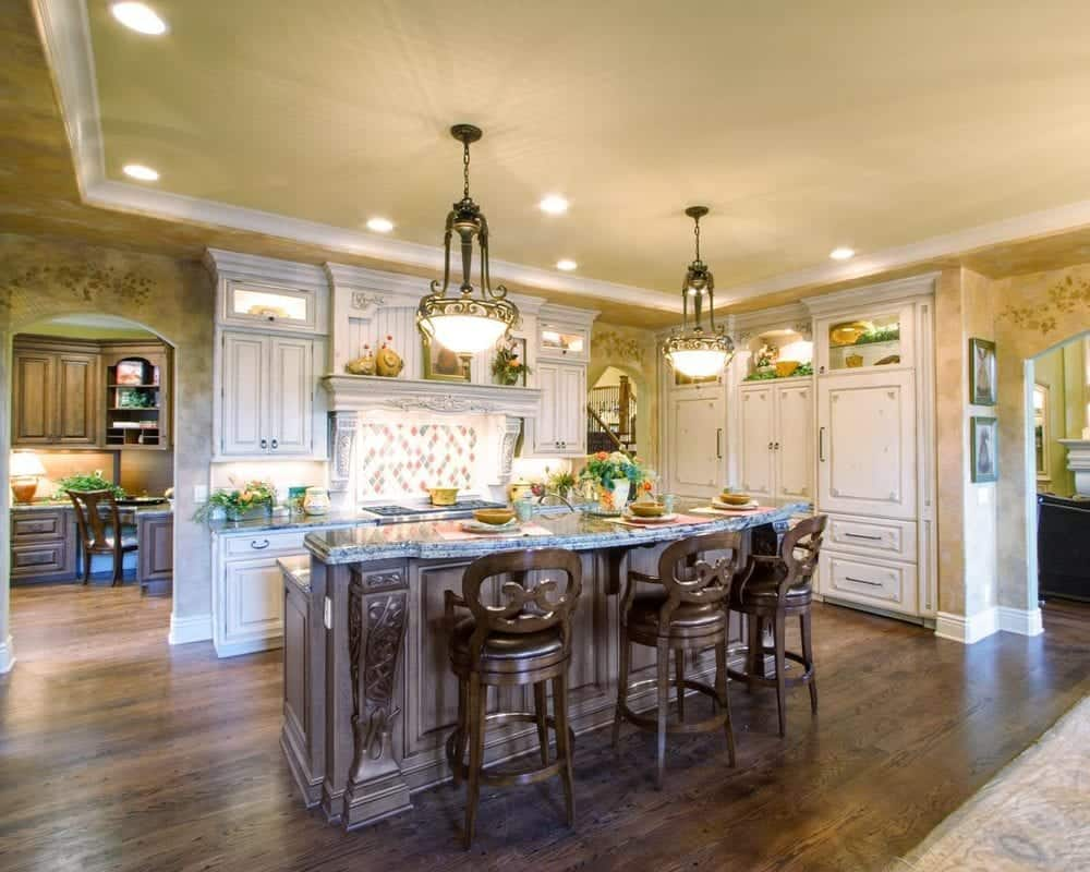 This warm and homey kitchen has a large dark brown wooden kitchen island that is paired with wooden stools of the same hue for a breakfast bar. This matches well with the hardwood flooring.