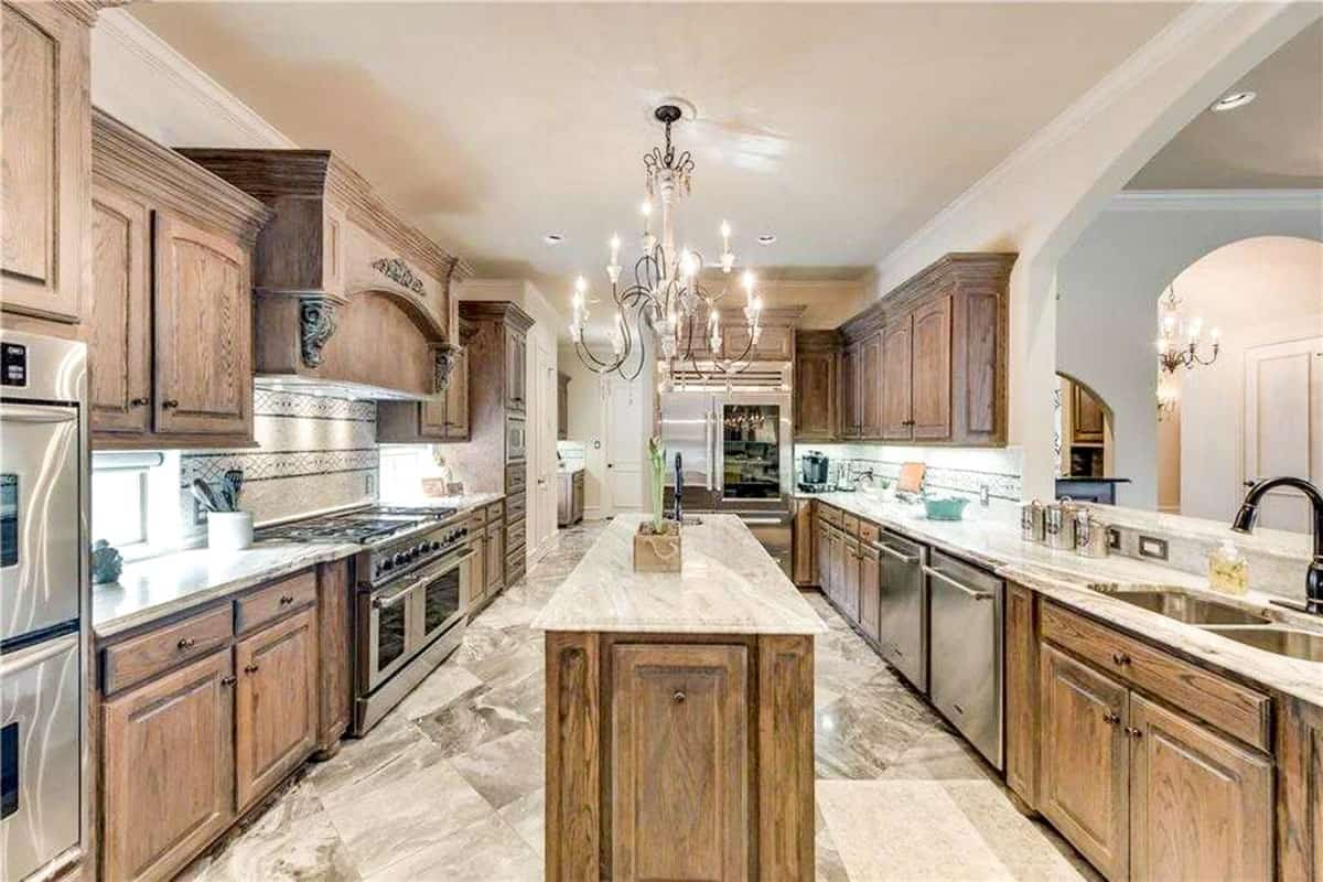 This galley kitchen is equipped with stainless steel appliances, a marble top island, and dual sink paired with a goose-neck faucet. The narrow kitchen island is topped with an intricate chandelier.
