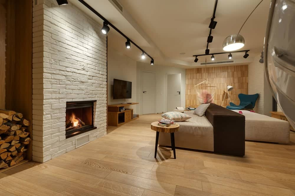 This is a close look at the home theater of the house that has a large two-way sofa across from the brick fireplace and the wall-mounted TV. These are then topped with modern industrial-style lighting on the ceiling.
