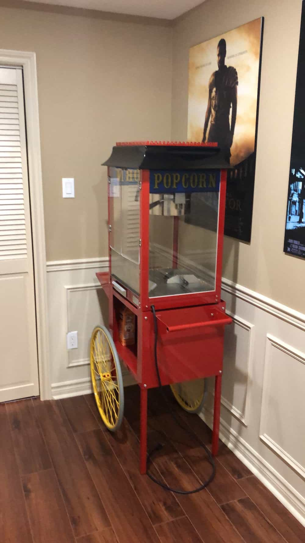 Red cart style popcorn maker next to home theater