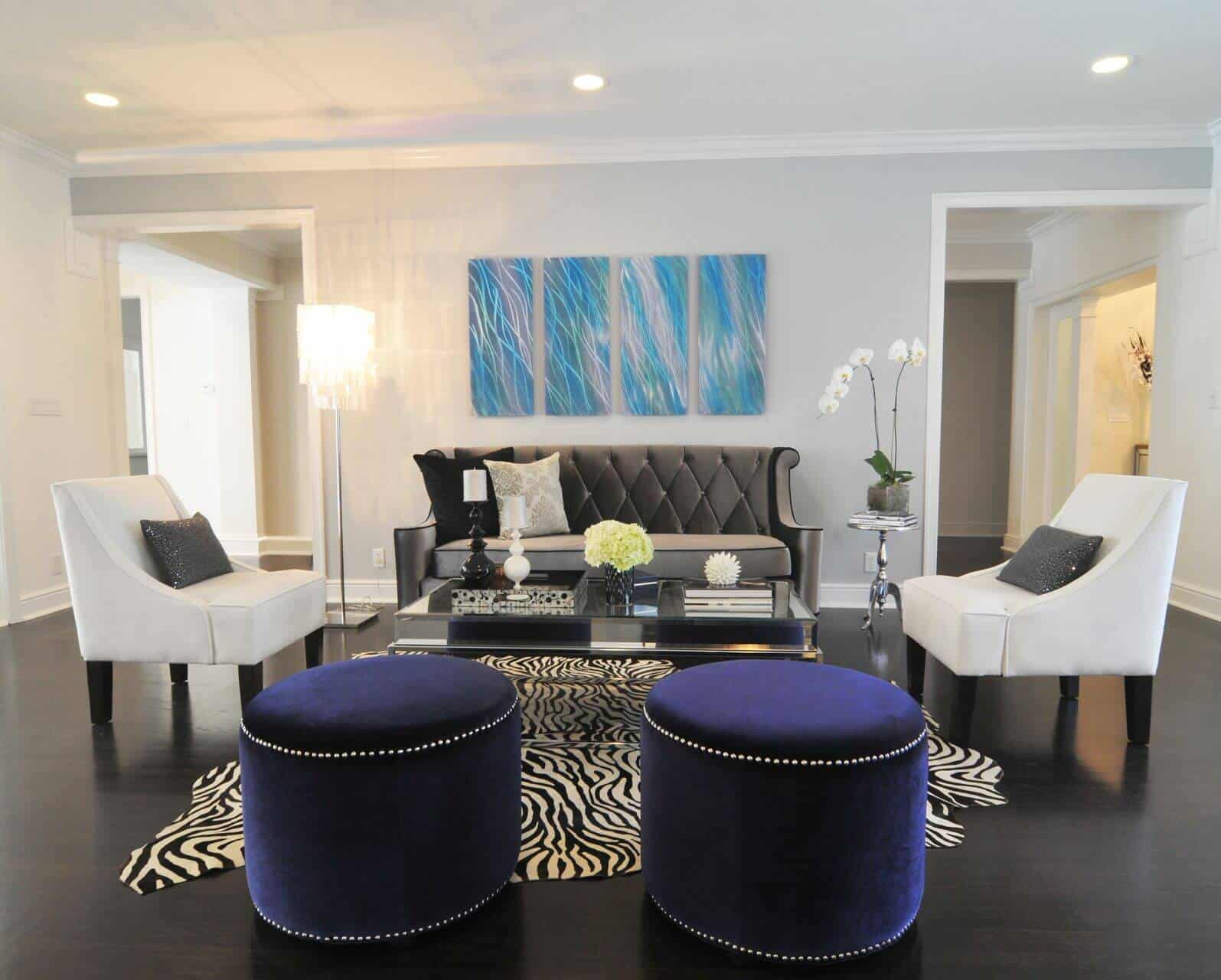 A living room boasting classy white and black seats with a pair of handsome-looking ottomans and a zebra rug.