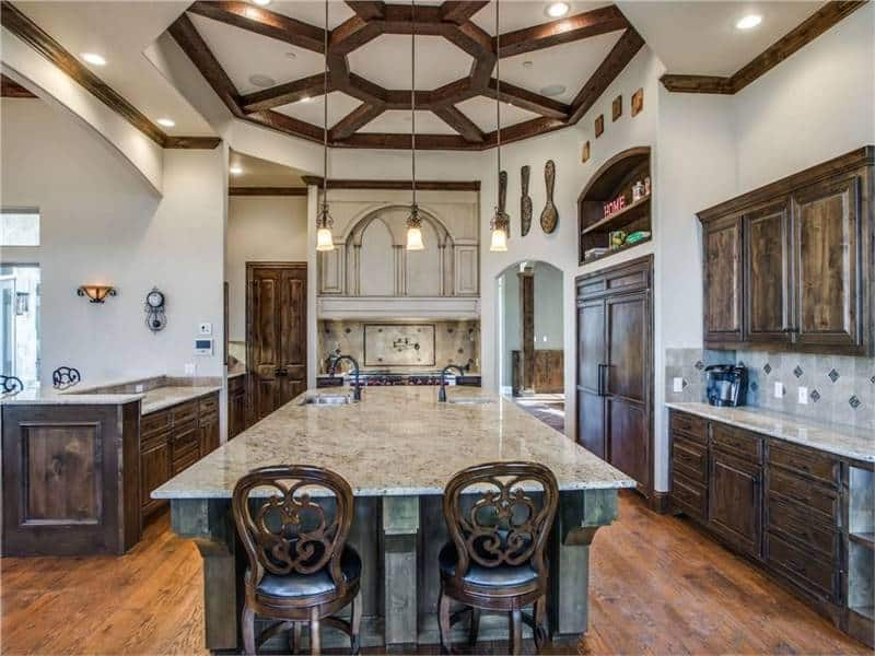 The elegant tray ceiling of this kitchen has wood accents that match with the tone of the cabinetry that stands out against the earthy beige walls.
