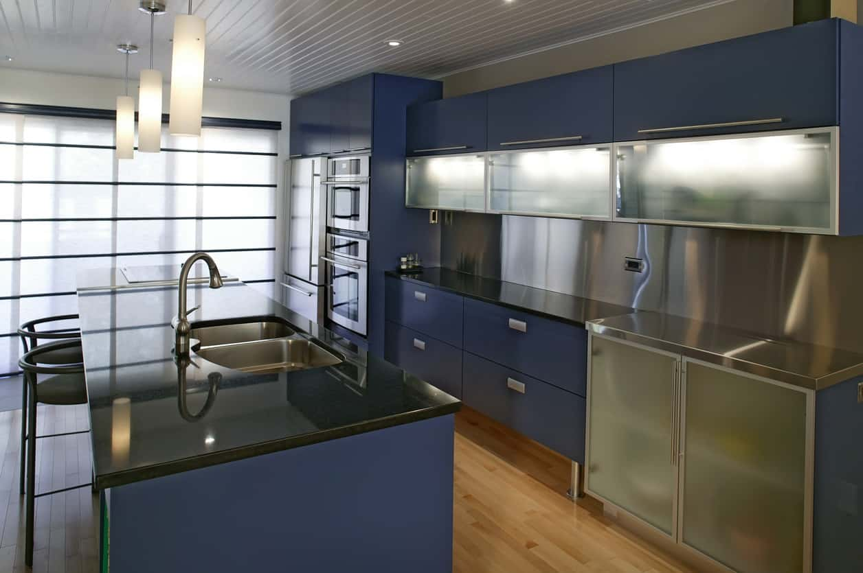 Dark blue kitchen cabinets with black countertops, brushed glass cabinets and stainless steel appliances