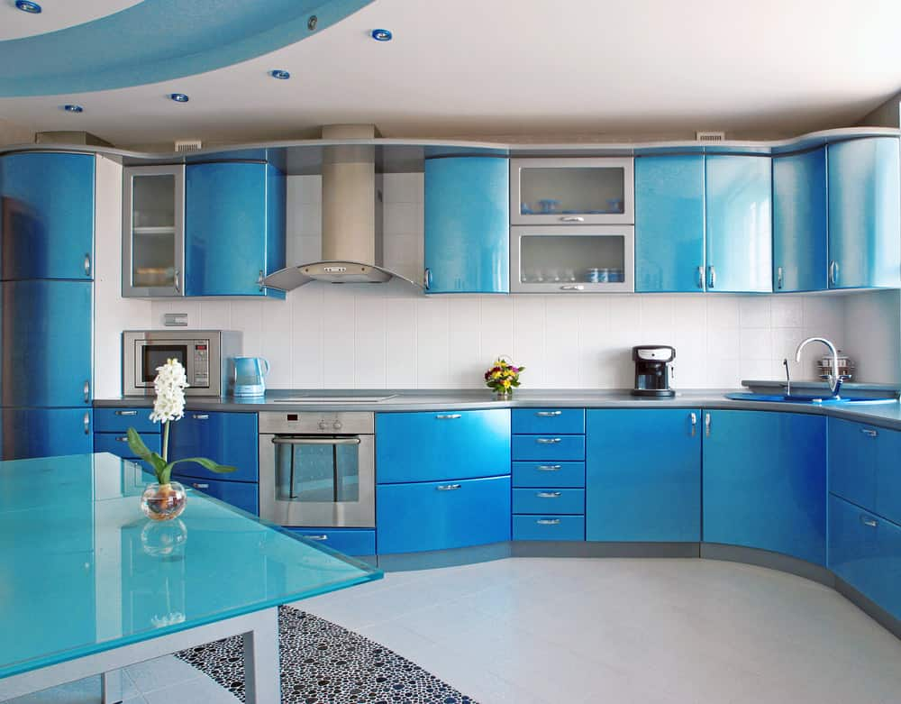 Metallic blue rounded kitchen cabinets with blue recessed lights and tray ceiling