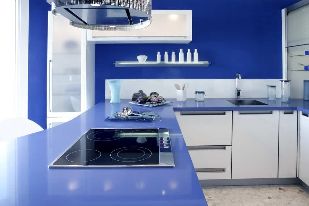 Bright blue walls and countertops give this kitchen an aquatic style