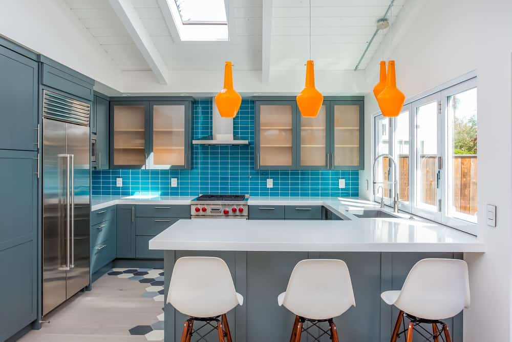 Turquoise blue backsplash looks decent with gray-blue cabinets in this kitchen that also features bright orange pendant lights