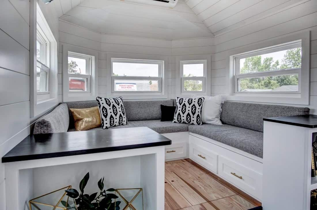 Close up photo of large u-shaped gray and white sectional sofa in tiny house