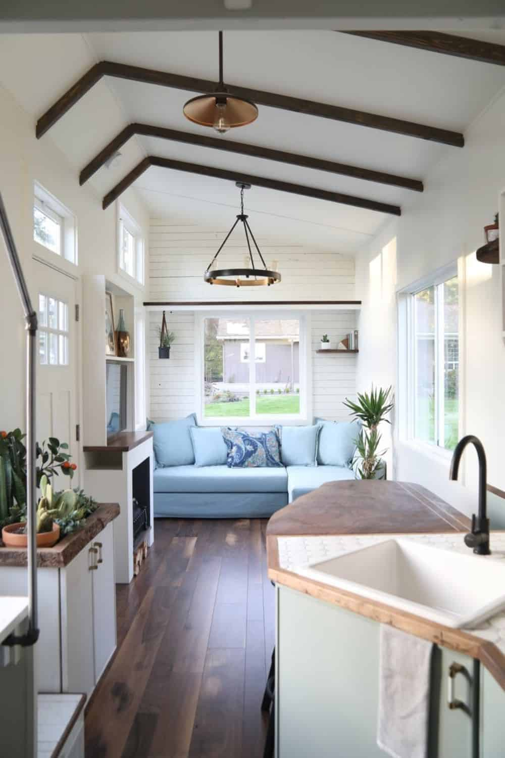 Tiny house with wood beamed ceiling, sectional sofa and dark wood flooring.