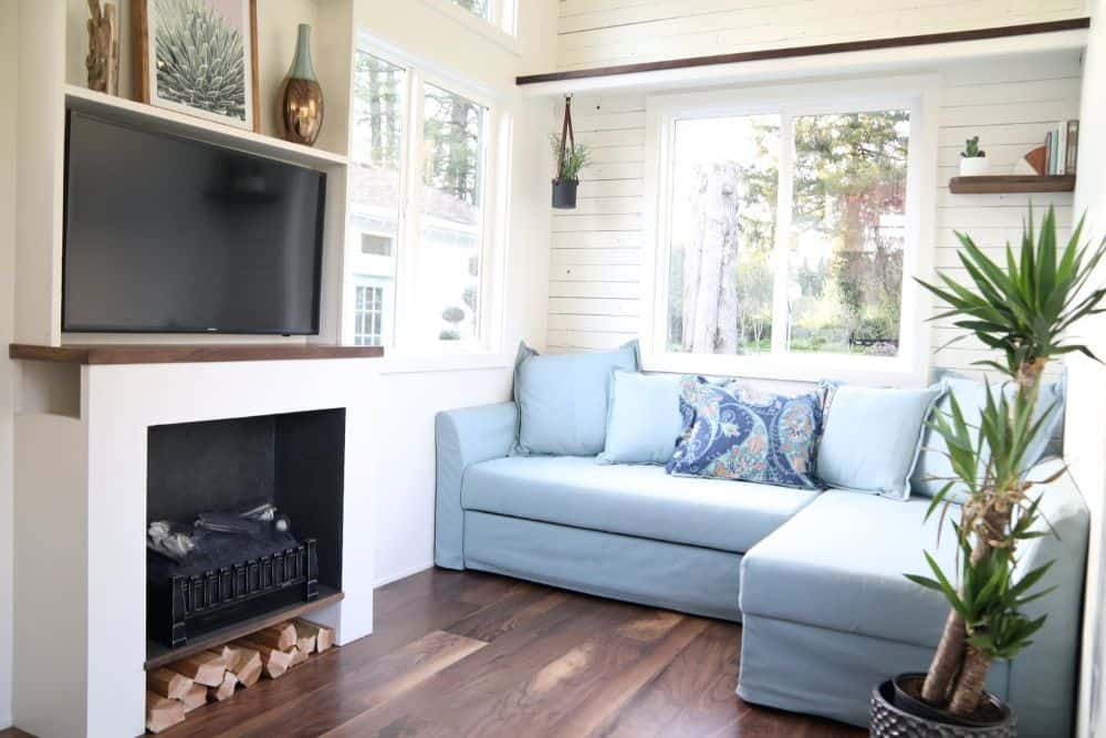 Tiny house with blue chaise sectional sofa under a large window