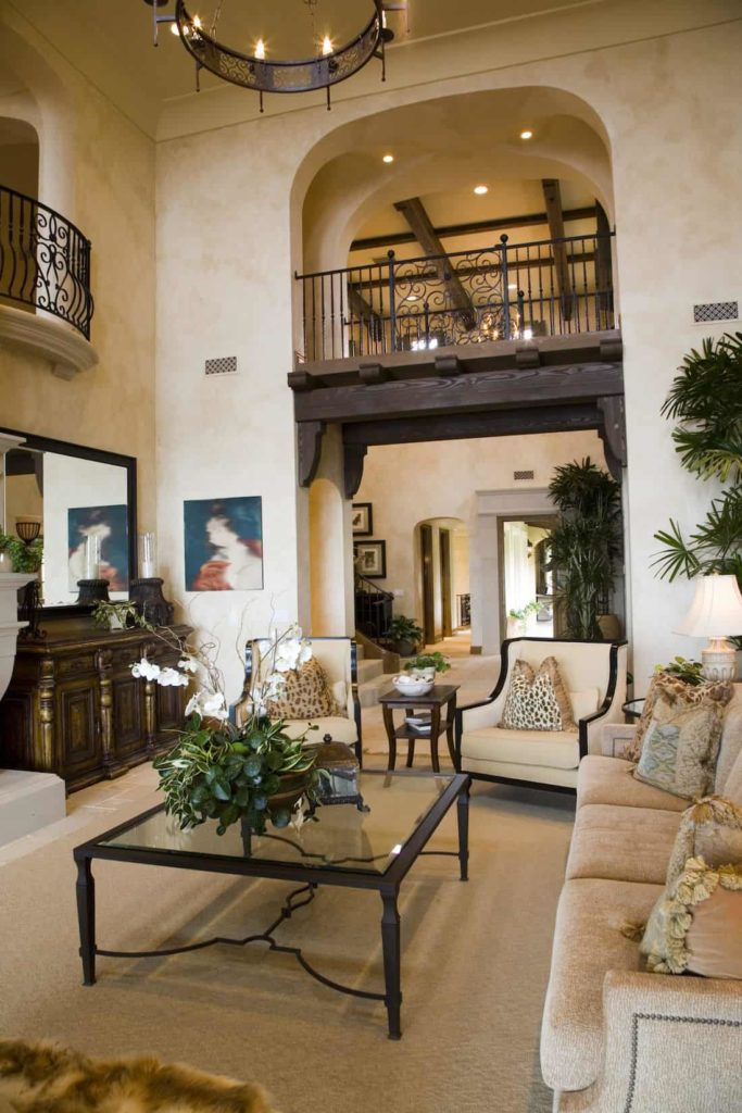 The tall beige ceiling of this living room hangs a round wrought iron chandelier over the glass-top coffee table paired with a beige sofa and a pair of beige cushioned chairs. This angle allows for a view of the second floor indoor balconies with wrought iron railings contrasting the beige walls.