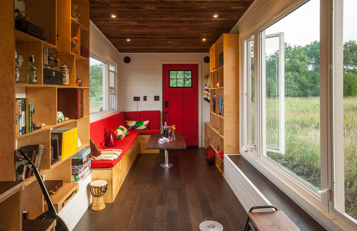 Long tiny house living room with long red built-in l-shaped sectional sofa with coffee table and bookshelves