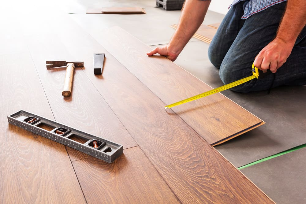 Man installing laminate flooring in living room