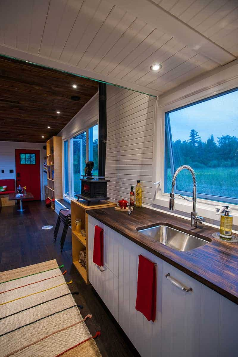 I love the dark wood countertops against the white cabinetry and white walls/ceiling. The large window above the sink is also a great feature because it can get dark in some tiny homes.