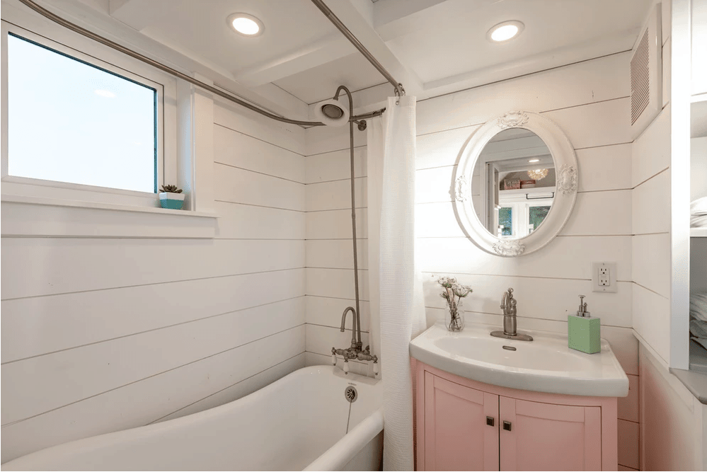 Cozy white and pink tiny house bathroom with tub/shower, large vanity, sink, nautical mirror and coffered ceiling with recessed lights.