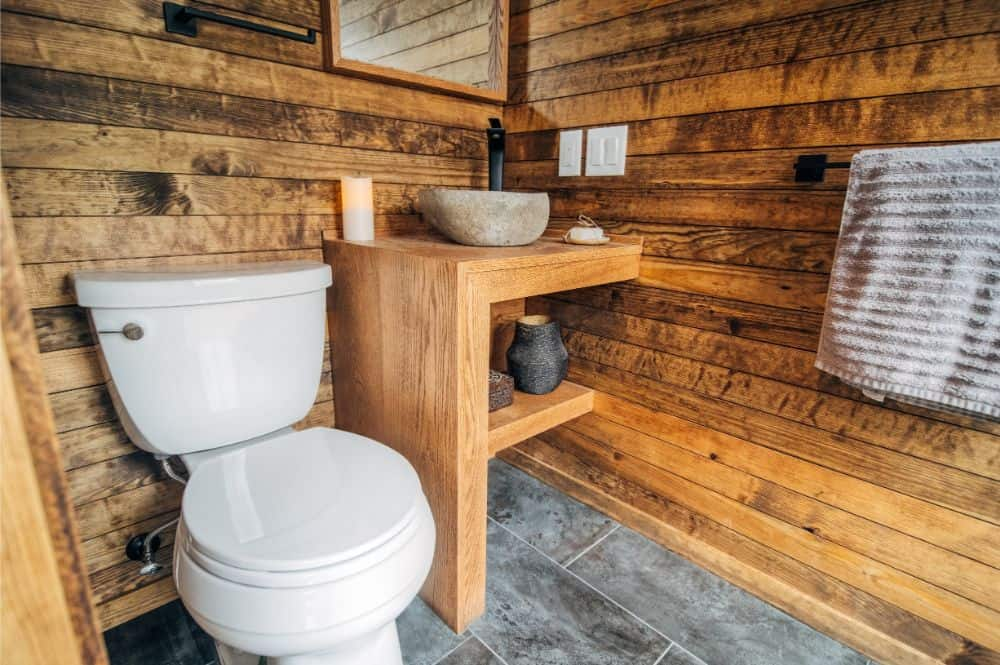 Rustic bathroom in a tiny house with distressed wood walls, custom wood vanity with concrete vessel basin next to a white toilet.