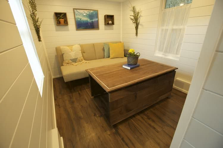 Separate living room space with futon sofa and coffee table in tiny house