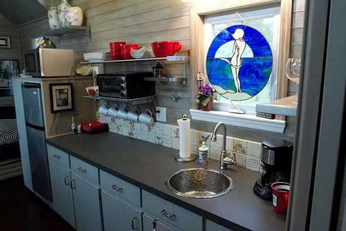 This kitchen is fairly long with decent counterspace, a round sink, open shelving and a half-decently sized refrigerator.