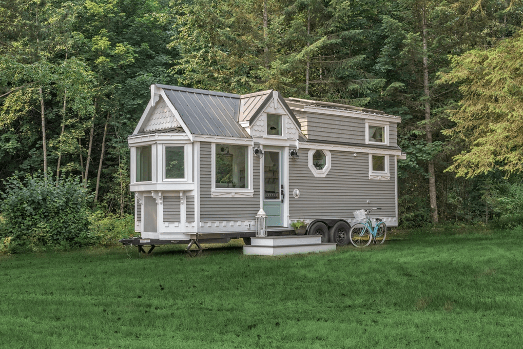 This gray tiny house with white trim is built in a traditional