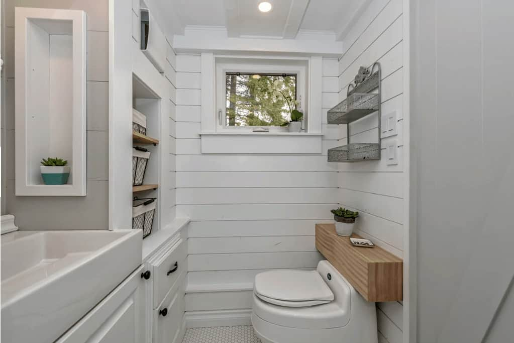 Photo of the toilet and trough-style bathroom sink. This tiny house bathroom includes plenty of storage as well.