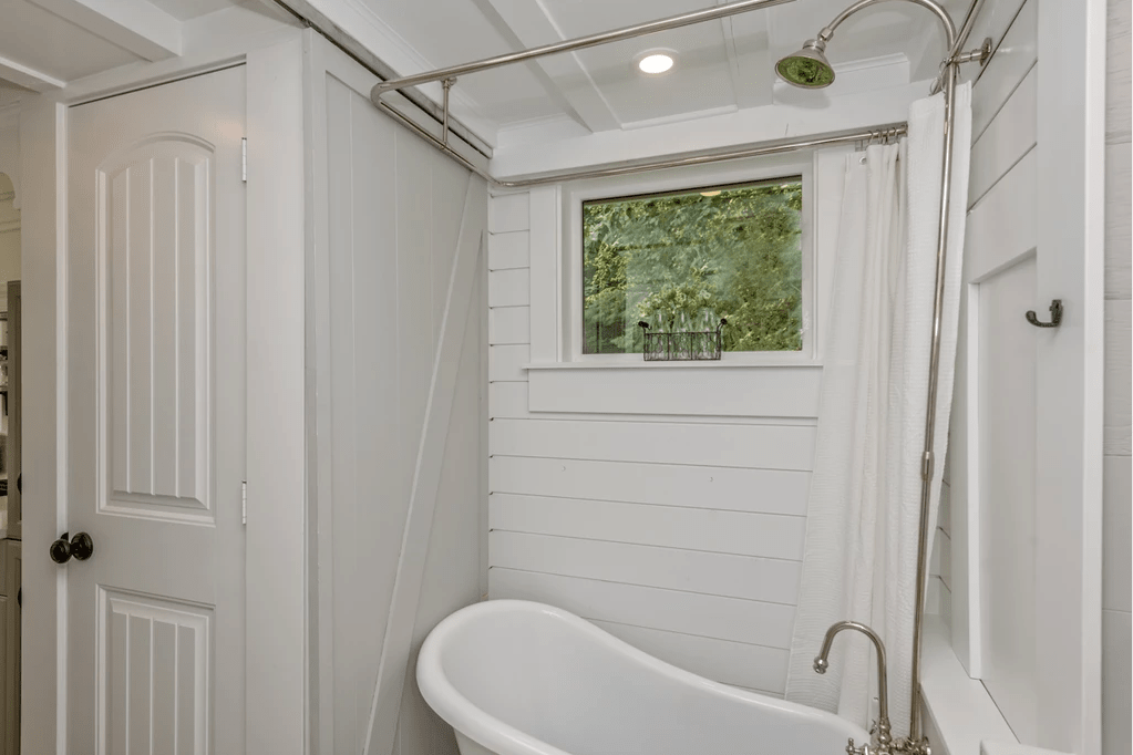 Small freestanding bathtub with shower attachment in a tiny home bathroom.