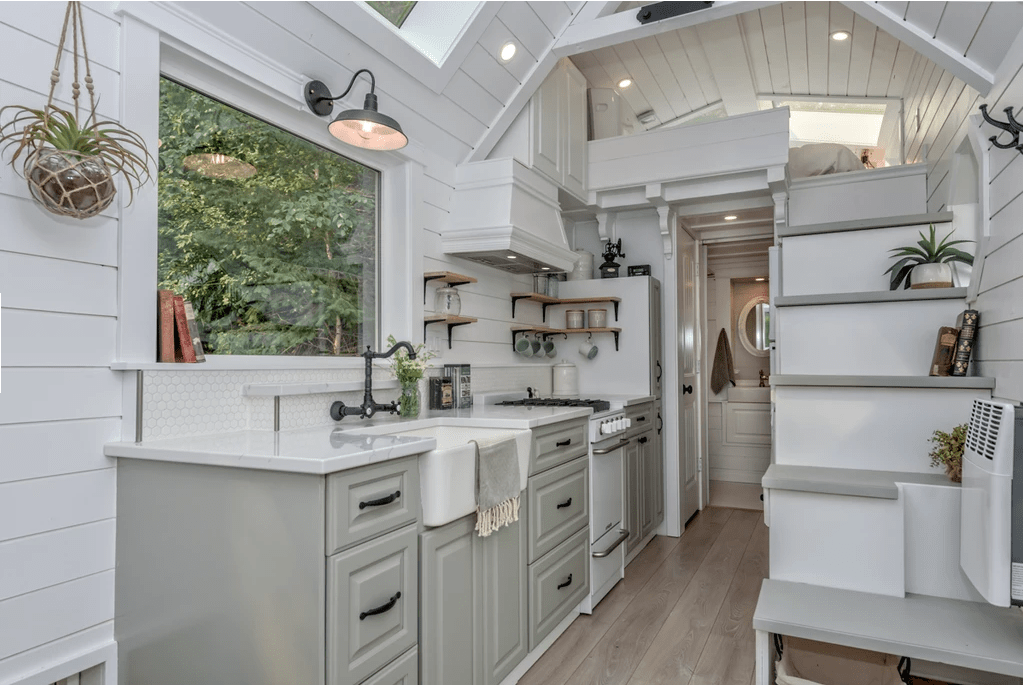 Tiny house with light gray cabinets, white countertops that includes a white oven and range as well as a large white farmhouse sink. There's a large picture window above the sink as well as a skylight above the kitchen placed in the cathedral ceiling.