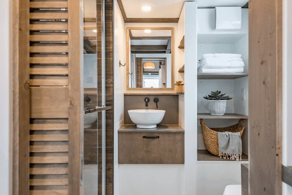 Tiny house bathroom with glass-shower, vessel sink with modern faucet, wood trim on the ceiling and stylish built-in shelving.