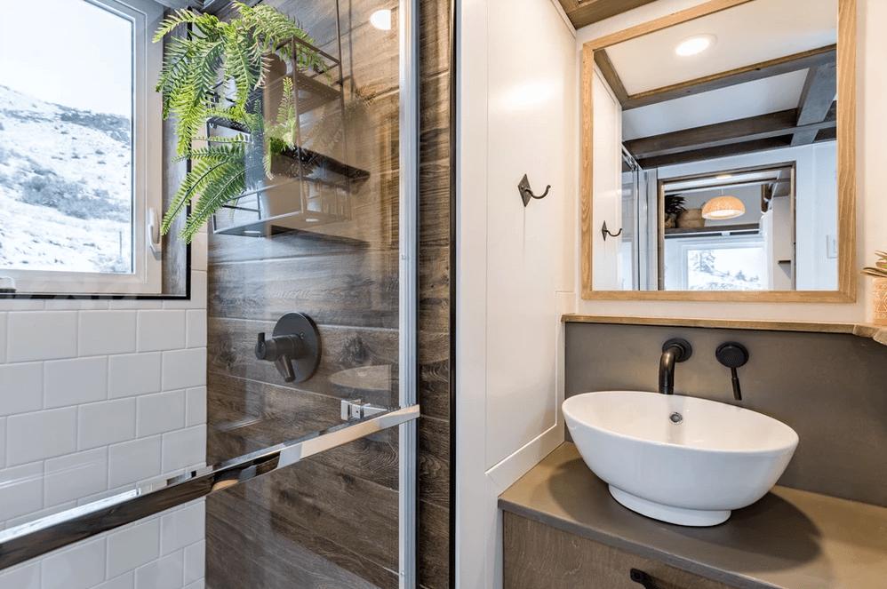 I love the dark wood paneling on the shower wall which looks great with the white tile on other shower walls. Shower includes a window which emits plenty of light into the bathroom - hence the glass shower door.