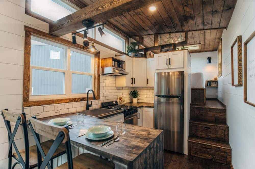 Stunning rustic tiny house kitchen with dark wood countertops, dark wood ceiling, white subway tile and stainless steel appliances. Includes peninsula breakfast bar.